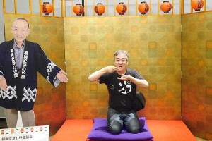 落語ミュージアムで、笑点の座布団に座ってはしゃぐおじさん。